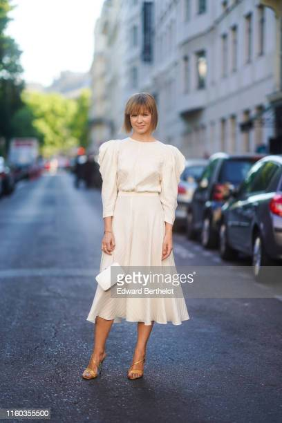 Vika Gazinskaya wears a white pleated dress with shoulder pads, a bag, golden shoes outside Valentino, during Paris Fashion Week -Haute Couture...