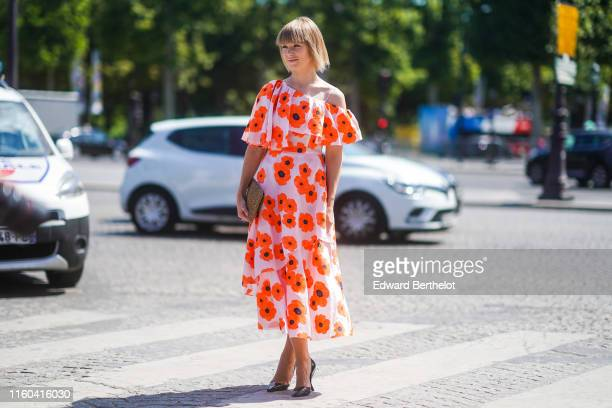 Vika Gazinskaya wears an offshoulder white and orange floral print dress heels shoes outside Chanel during Paris Fashion Week Haute Couture...