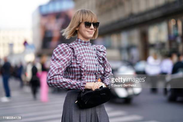 Vika Gazinskaya wears sunglasses, a ruffle top with shoulder pads and checked printed patterns, a gray pleated skirt, outside Balmain, during Paris...