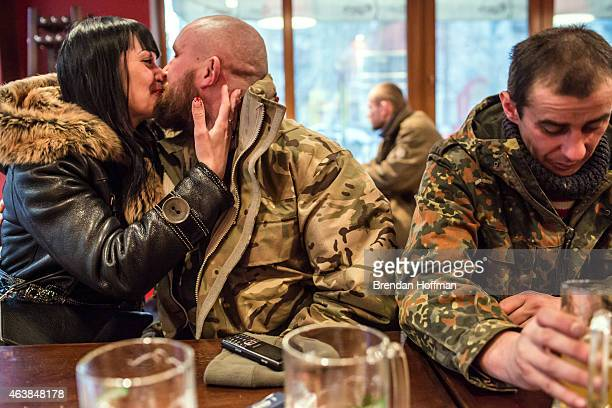 Vika kisses her friend Kolya as fellow soldier Sergei drinks a beer at a local pizza restaurant after their unit withdrew from Debaltseve on February...
