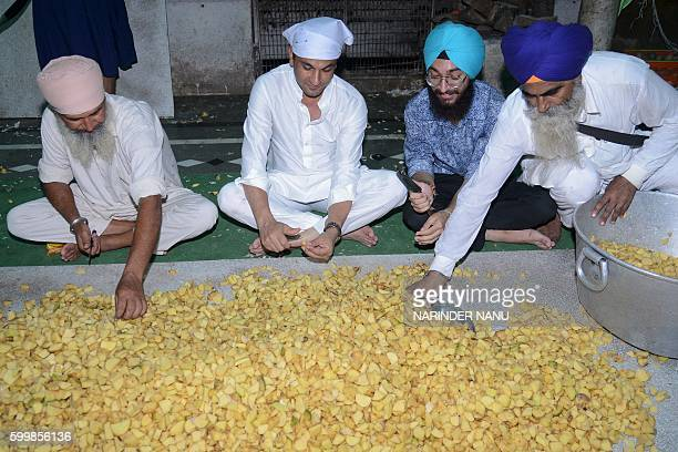 Vikas Khanna MasterChef India host and executive chef of Junoon restaurant in New York cuts potatoes for a communal vegetarian meal known as 'langar'...