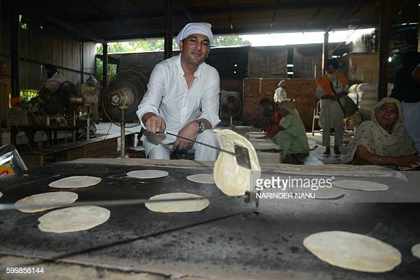 Vikas Khanna MasterChef India host and executive chef of Junoon restaurant in New York prepare chappati for a communal vegetarian meal known as...