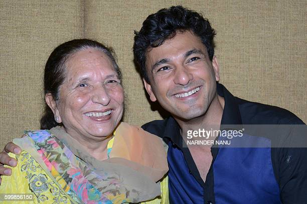 Vikas Khanna MasterChef India host and executive chef of Junoon restaurant in New York poses with his mother Bindu during a promotional event for the...