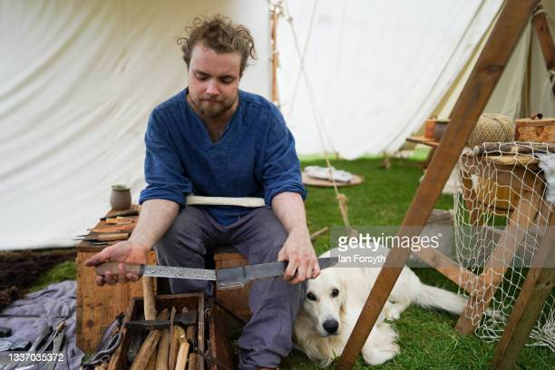 Viking blacksmith re-enactor works with his dog in the grounds of Whitby Abbey on August 29, 2021 in Whitby, England. Around 130 re-enactors gather...