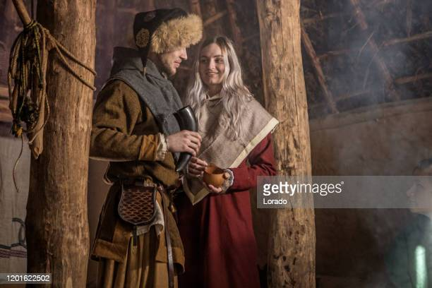 a viking couple in a viking settlement hall - medieval stock pictures, royalty-free photos & images