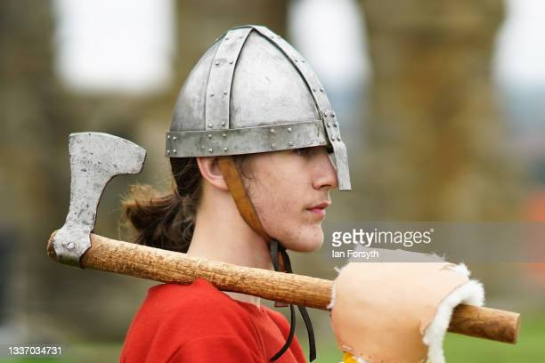 Viking re-enactor carries an axe as he prepares for a fighting demonstration in the grounds of Whitby Abbey on August 29, 2021 in Whitby, England....
