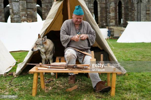 Viking re-enactor carves a wooden spoon as he sits outside his tent in the grounds of Whitby Abbey on August 29, 2021 in Whitby, England. Around 130...