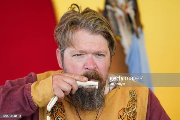 Viking re-enactor combs his beard as he sits in his tent in the grounds of Whitby Abbey on August 29, 2021 in Whitby, England. Around 130 re-enactors...