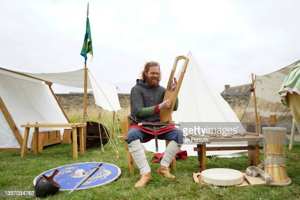 Viking re-enactor plays a musical instrument as he sits in camp in the grounds of Whitby Abbey on August 29, 2021 in Whitby, England. Around 130...