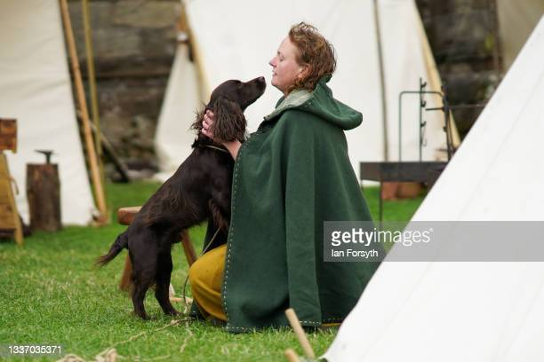 Viking re-enactor plays with her dog in the grounds of Whitby Abbey on August 29, 2021 in Whitby, England. Around 130 re-enactors gather at Whitby...