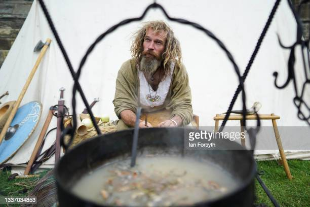 Viking re-enactor prepares a stew over a fire in the grounds of Whitby Abbey on August 29, 2021 in Whitby, England. Around 130 re-enactors gather at...