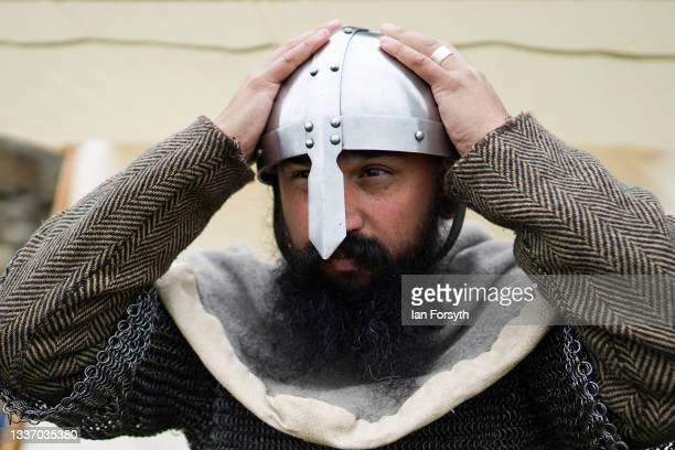 Viking re-enactor secures his helmet before taking part in a fighting demonstration in the grounds of Whitby Abbey on August 29, 2021 in Whitby,...