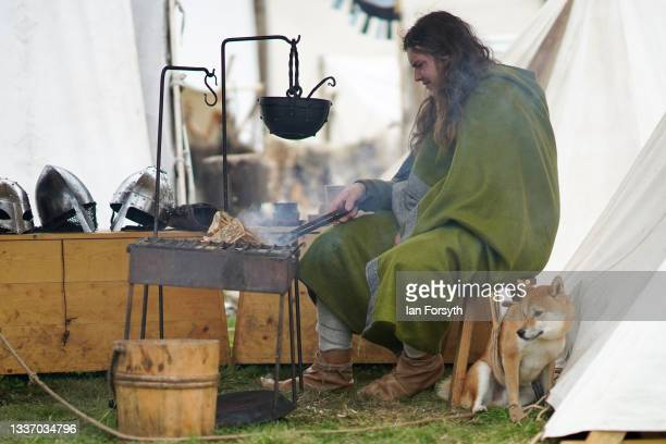 Viking re-enactor sits with his dog as he cooks his breakfast in the grounds of Whitby Abbey on August 29, 2021 in Whitby, England. Around 130...