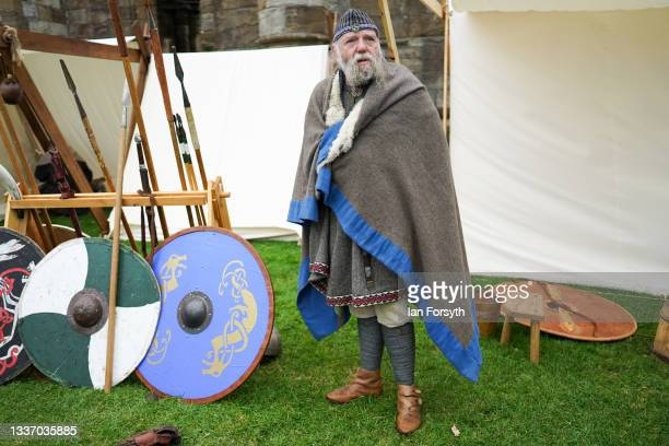 Viking re-enactor stands next to shields and weapons in the grounds of Whitby Abbey on August 29, 2021 in Whitby, England. Around 130 re-enactors...