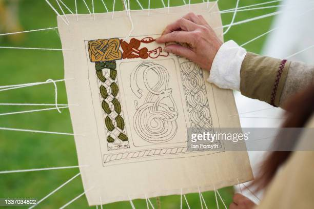 Viking re-enactor works on a piece of embroidery in the grounds of Whitby Abbey on August 29, 2021 in Whitby, England. Around 130 re-enactors gather...