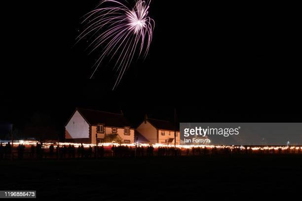 Viking reenactors and members of the public take part in a torchlit procession during New Year's Eve celebrations at the Flamborough Fire Festival on...