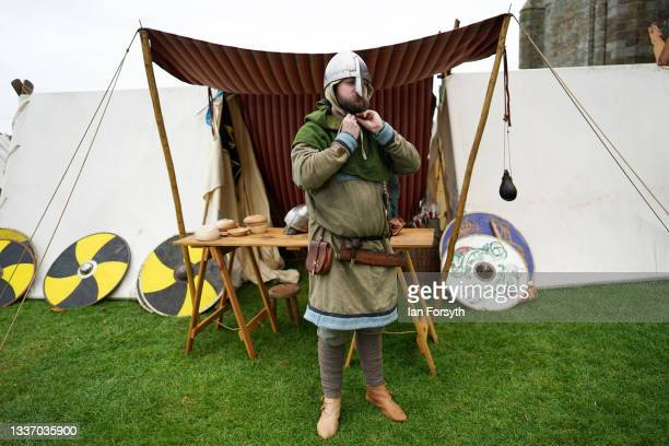 Viking re-enactors fastens his helmet in the grounds of Whitby Abbey on August 29, 2021 in Whitby, England. Around 130 re-enactors gather at Whitby...