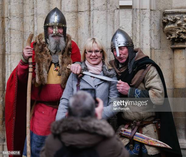 Viking re-enactors pose for a picture with a member of the public before they march to Coppergate in a show of strength before battle during a living...