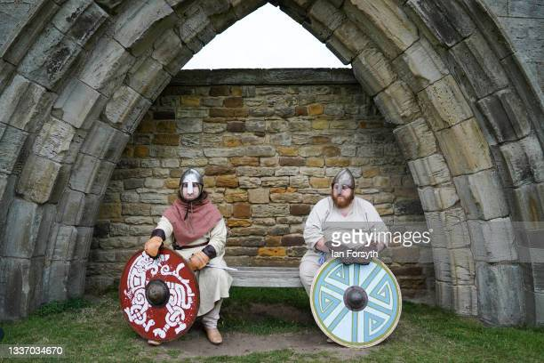 Viking re-enactors sit on a bench ahead of a battle in the grounds of Whitby Abbey on August 29, 2021 in Whitby, England. Around 130 re-enactors...
