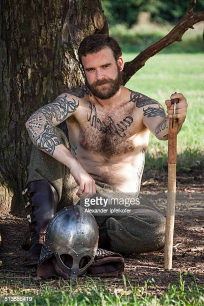 Viking resting under a tree with axe and helmet
