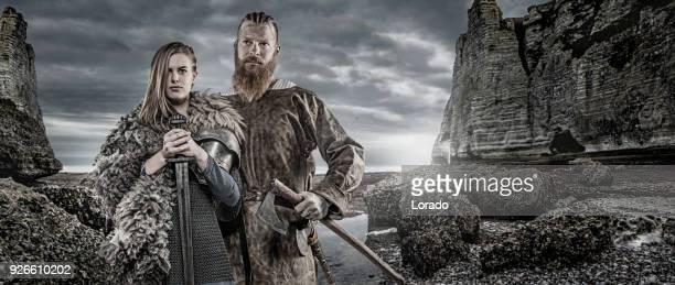Rey del Guerrero de Viking y princesa delante de tesoro Vikingo y gama de la montaña