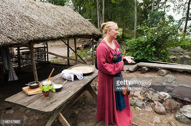 Viking woman with simple breadmaking equipment at the World Heritage Viking site of Birka on Bjorko Island.