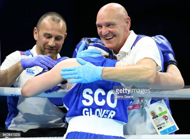 Vikki Glover of Scotland is congratulated by coach Mike Keane after beating Valerian Spicer of Dominica in the round of 16 bout on day three of the...