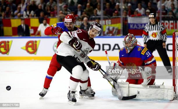 Viktor Antipin of Russia challenges Teodors Blugers of Latvia for the puck during the 2017 IIHF Ice Hockey World Championship game between Russia and...