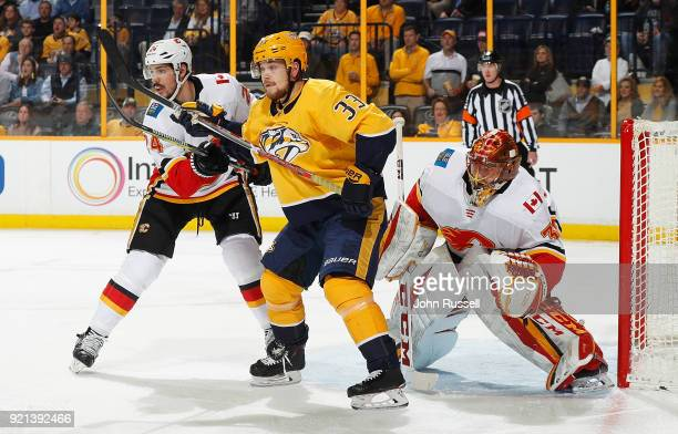 Viktor Arvidsson of the Nashville Predators battles between Travis Hamonic and David Rittich of the Calgary Flames during an NHL game at Bridgestone...