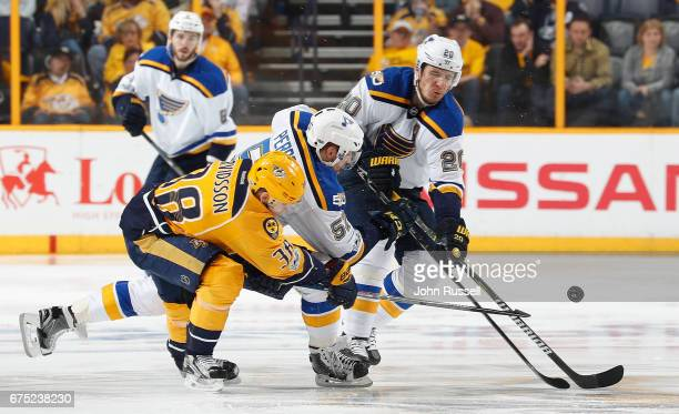 Viktor Arvidsson of the Nashville Predators battles for the puck against David Perron and Alexander Steen of the St Louis Blues in Game Three of the...
