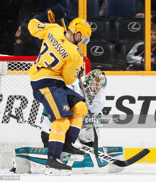 Viktor Arvidsson of the Nashville Predators battles in front of goalie Aaron Dell of the San Jose Sharks during an NHL game at Bridgestone Arena on...