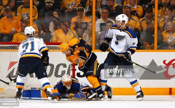 Viktor Arvidsson of the Nashville Predators gets checked by Joel Edmundson of the St Louis Blues in front of goalie Jake Allen in the second period...