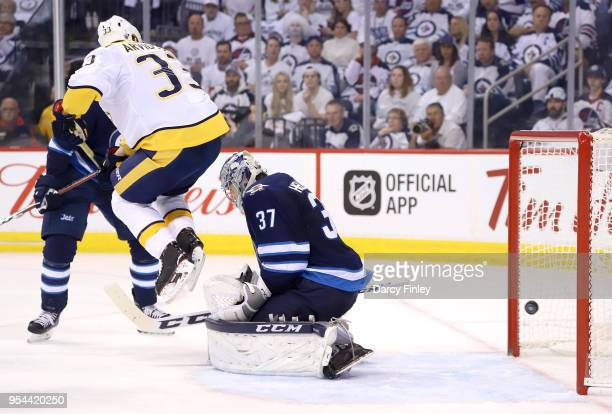 Viktor Arvidsson of the Nashville Predators leaps in the air as a shot by teammate PK Subban gets in behind goaltender Connor Hellebuyck of the...