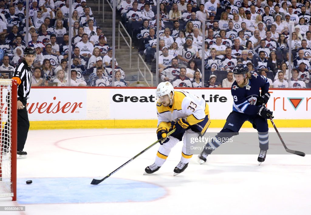 Viktor Arvidsson #33 of the Nashville Predators scores an empty net goal as Patrik Laine #29 of the Winnipeg Jets gives chase during third period action in Game Six of the Western Conference Second Round during the 2018 NHL Stanley Cup Playoffs at the Bell MTS Place on May 7, 2018 in Winnipeg, Manitoba, Canada.