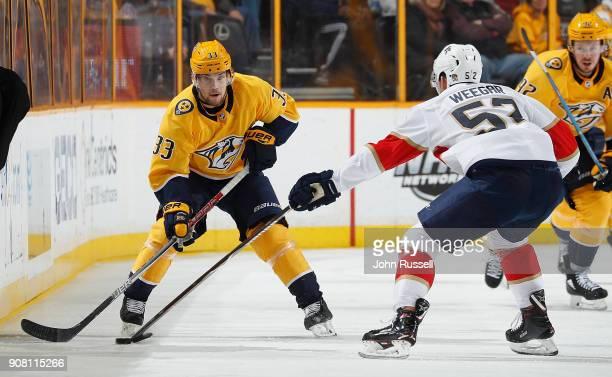 Viktor Arvidsson of the Nashville Predators skates against MacKenzie Weegar of the Florida Panthers during an NHL game at Bridgestone Arena on...