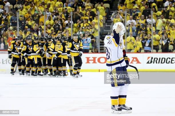 Viktor Arvidsson of the Nashville Predators skates off the ice as the Pittsburgh Penguins celebrate after defeating the Nashville Predators 53 in...
