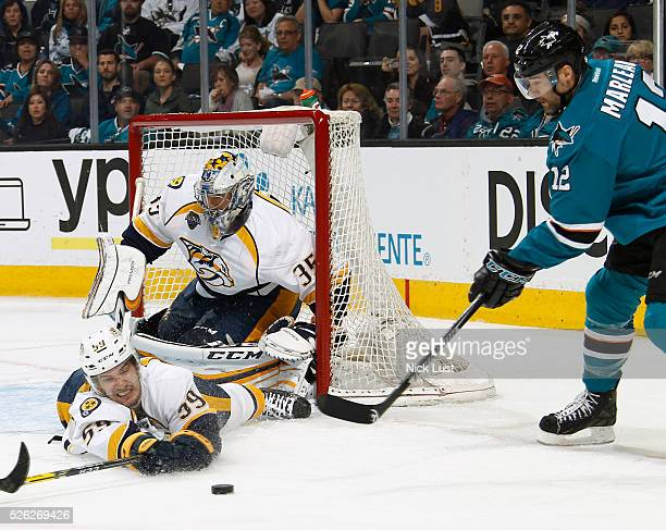 Viktor Arvidsson of the Nashville Predators slides to make the save on a shot by Patrick Marleau of the San Jose Sharks in front of Pekka Rinne of...