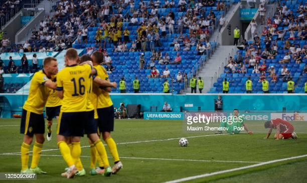 Viktor Claesson of Sweden celebrates with teammates after scoring their side's third goal as Wojciech Szczesny and Bartosz Bereszynski of Poland...