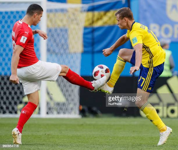 Viktor Claesson of Sweden national team and Granit Xhaka of Switzerland national team vie for the ball during the 2018 FIFA World Cup Russia Round of...