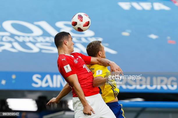 Viktor Claesson of Sweden national team and Granit Xhaka of Switzerland national team vie for a header during the 2018 FIFA World Cup Russia Round of...