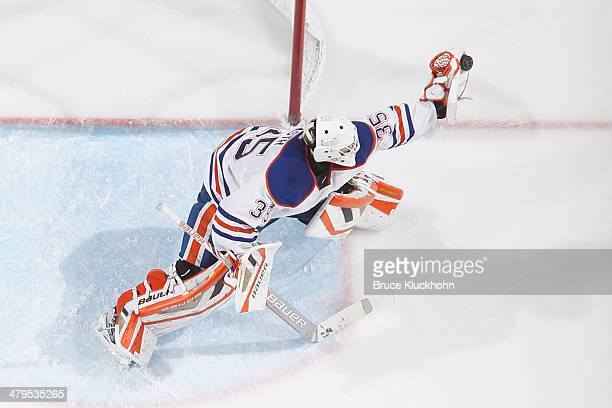 Viktor Fasth of the Edmonton Oilers makes a glove save during the game against the Minnesota Wild on March 11 2014 at the Xcel Energy Center in St...