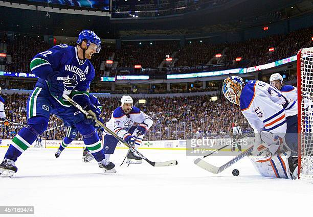 Viktor Fasth of the Edmonton Oilers makes a save off the shot of Daniel Sedin of the Vancouver Canucks during their NHL game at Rogers Arena October...