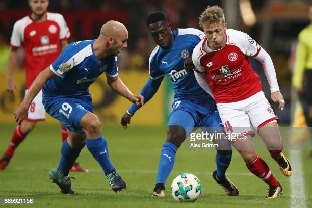 Viktor Fischer of Mainz is challenged by Kingsley Schindler and Patrick Herrmann of Kiel during the DFB Cup match between 1 FSV Mainz 05 and Holstein...