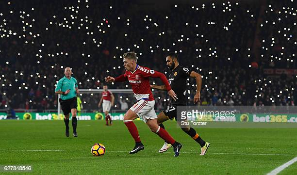 Viktor Fischer of Middlesbrough is chased by Ahmed Elmohamady of Hull City as fans light up the stadium during the Premier League match between...