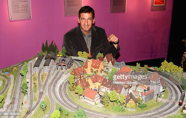 Viktor Gernot poses next to a toy train of Peter Alexander during a press event for the Peter Alexander charity auction at Madame Tussauds on October...