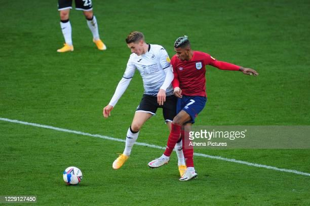 Viktor Gyökeres of Swansea Citybattles with Juninho Bacuna of Huddersfield Town during the Sky Bet Championship match between Swansea City and...