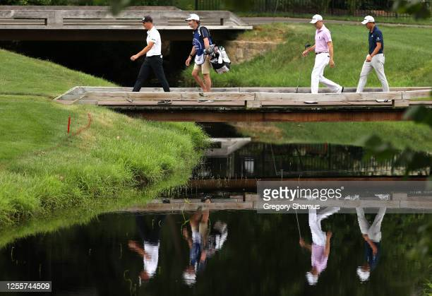 Viktor Hovland of Norway Justin Thomas of the United States and Collin Morikawa of the United States walk across a bridge on the sixth hole during...