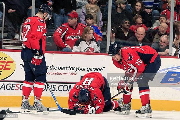 Viktor Kozlov of the Washington Capitals and teammate Mike Green check on Alexander Ovechkin after he took a hard hit to the knee on February 24 2008...