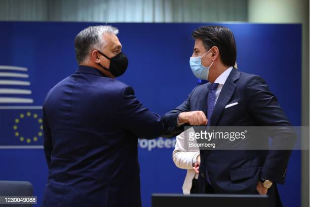 Viktor Orban, Hungary's prime minister, left, greets Giuseppe Conte, Italys prim minister, with an elbow bump during a roundtable meeting at a...