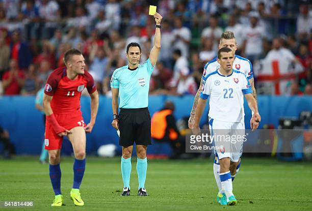 Viktor Pecovsky of Slovakia is shown a yellow card by Referee Carlos Velasco Carballo during the UEFA EURO 2016 Group B match between Slovakia and...